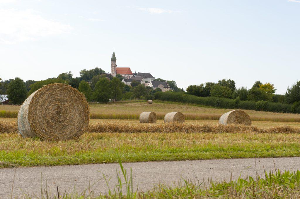 Feld mit Strohballen und das Kloster Andechs im Hintergrund