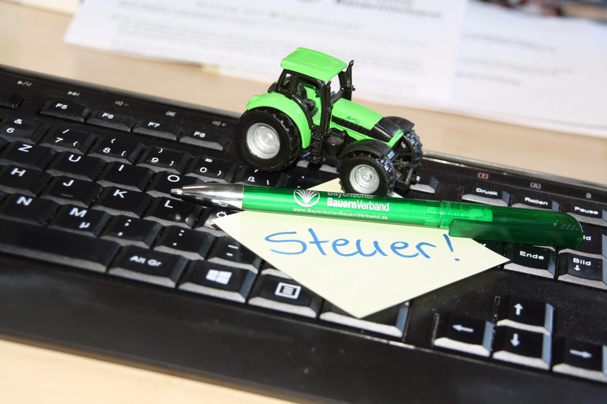 Ein kleiner grüner Traktor, ein grüner Kugelschreiber und ein Notizzettel mit der Aufschrift Steuer liegen auf einer Computertastatur.