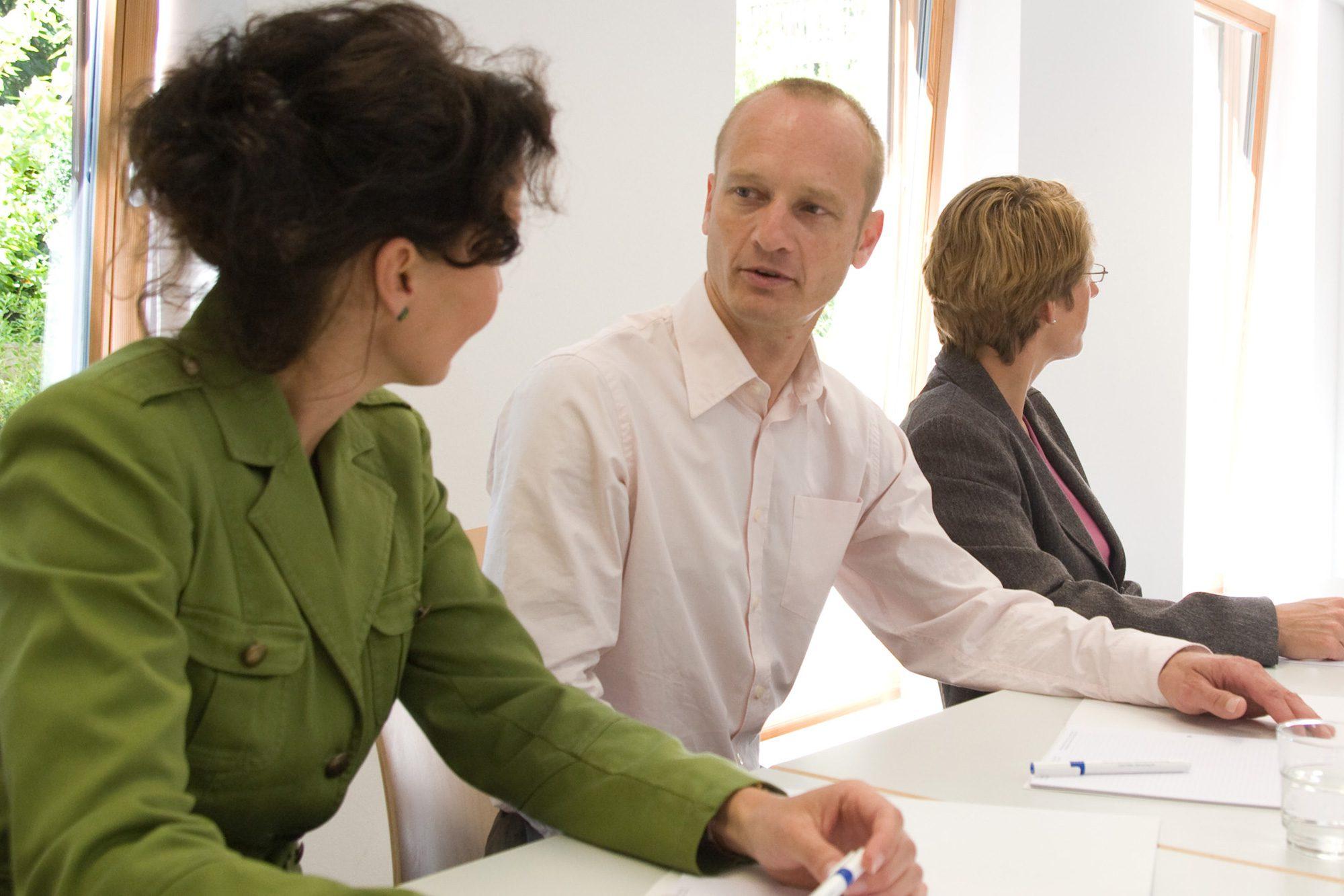 Eine Frau und ein Mann unterhalten sich am Tisch sitzend und eine andere Frau sieht in eine andere Richtung