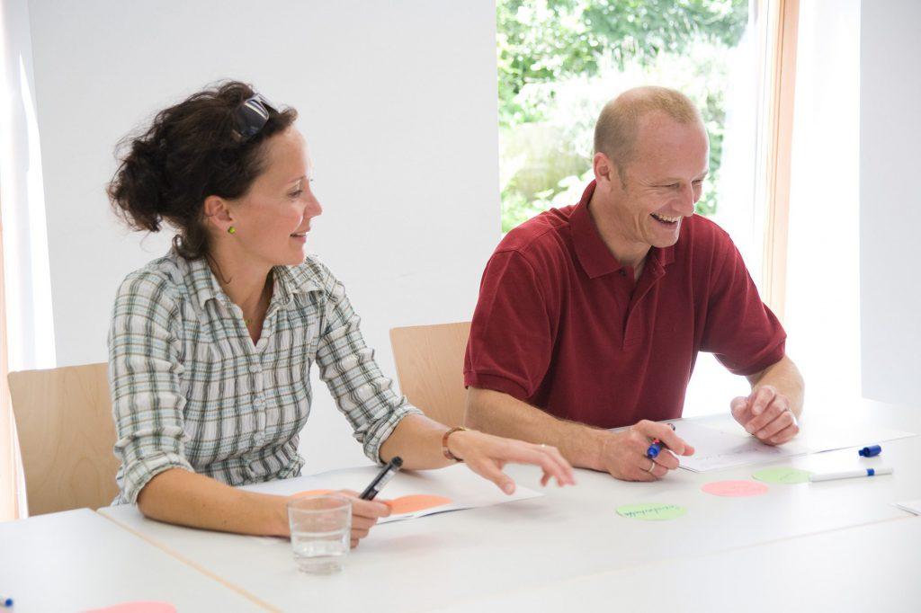 Zwei lachende Personen sitzen Am Tisch mit runden Klebezetteln und halten einen Stift in der Hand