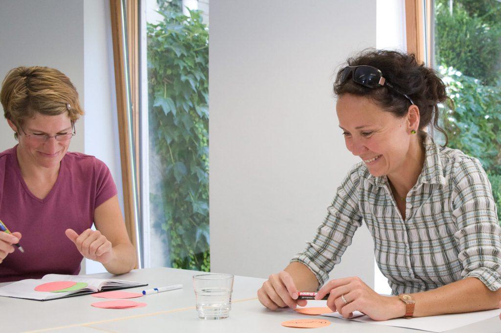 Zwei lächelnde Frauen sitzen am Tisch und beschreiben runde Klebezettel