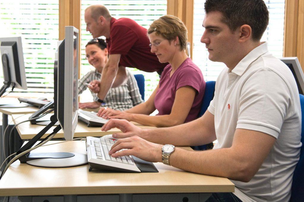 Vier Personen arbeiten in einem Computerraum