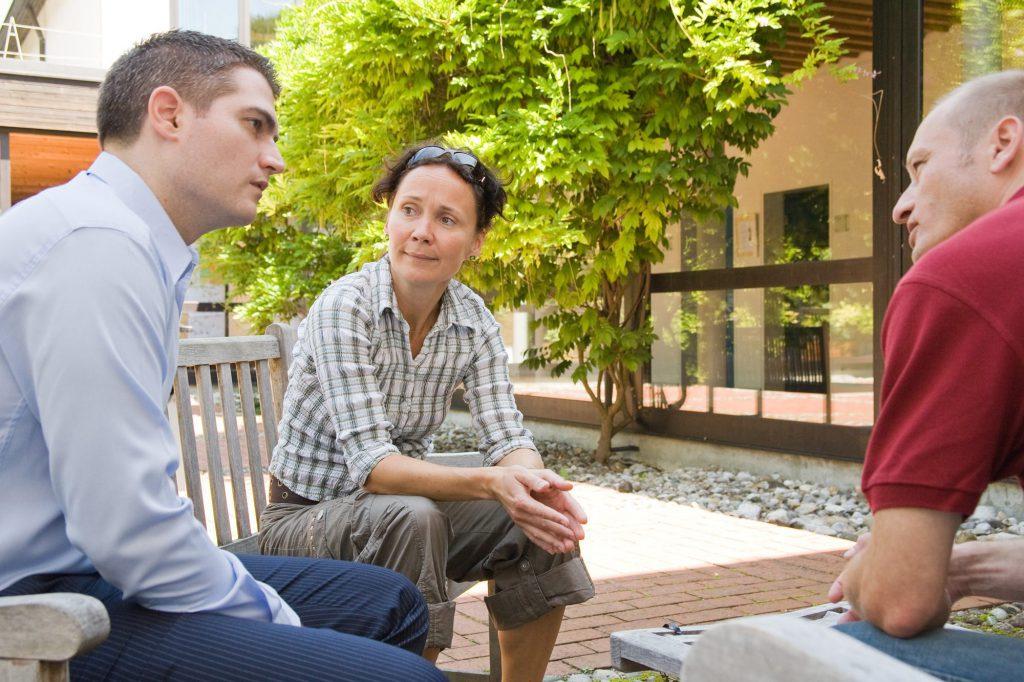 Zwei Männer und eine Frau sitzen draußen auf Holzbänken und unterhalten sich