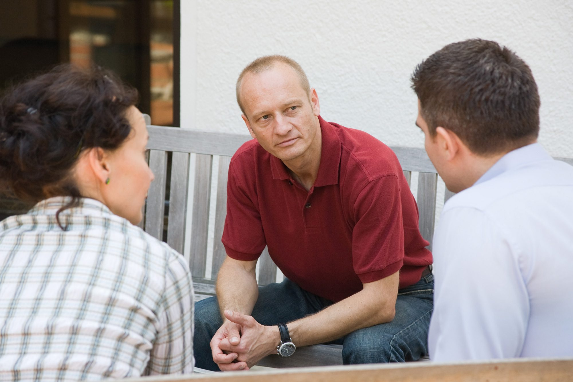 Drei Personen sitzen sich gegenüber und unterhalten sich