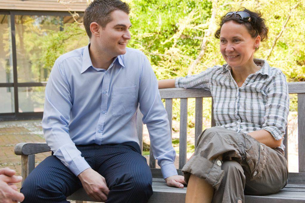 Ein Mann und eine Frau sitzen im Freiem auf einer Holzbank mit grünen Bäumen im Hintergrund