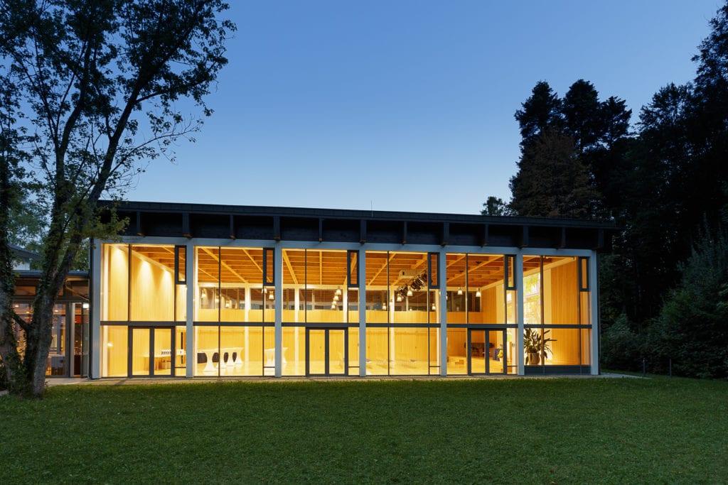 Beleuchteter großer Vortragssaal von außen durch die Fensterfront fotografiert