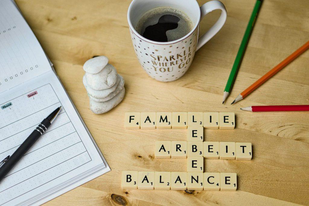 Utensilien zur besseren Planung, eine Tasse mit Kaffen neben übereinander liegenden kleinen Steinen und Scrabble Wörtern, die auf die Work-Life-Balance hinweisen.