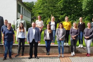 Gruppenfoto und im Hintergrund das Bildungshaus und Bäume