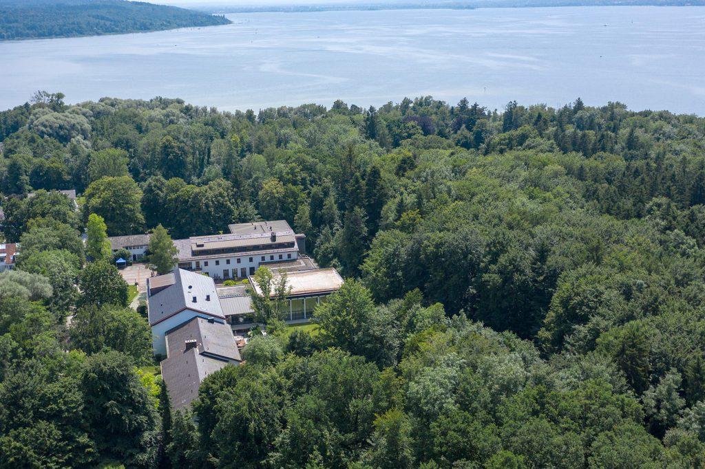 Das Bildungshaus von oben fotografiert, umgeben von Wald und dem Ammersee