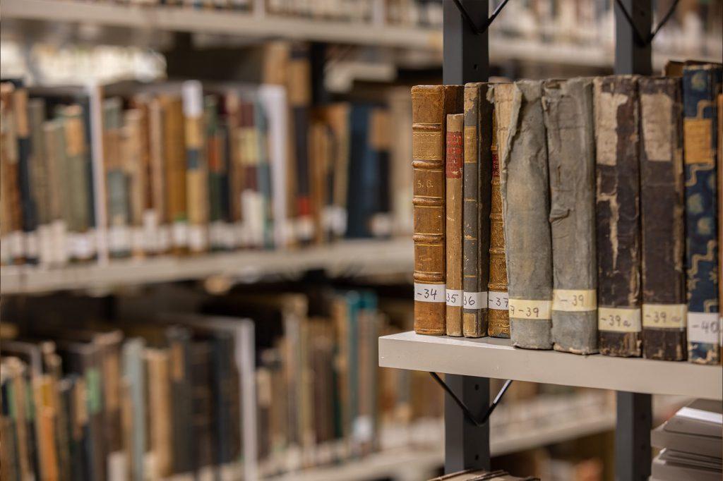 Alte historische Buchrücken und im Hintergrund Regale mit alten Büchern