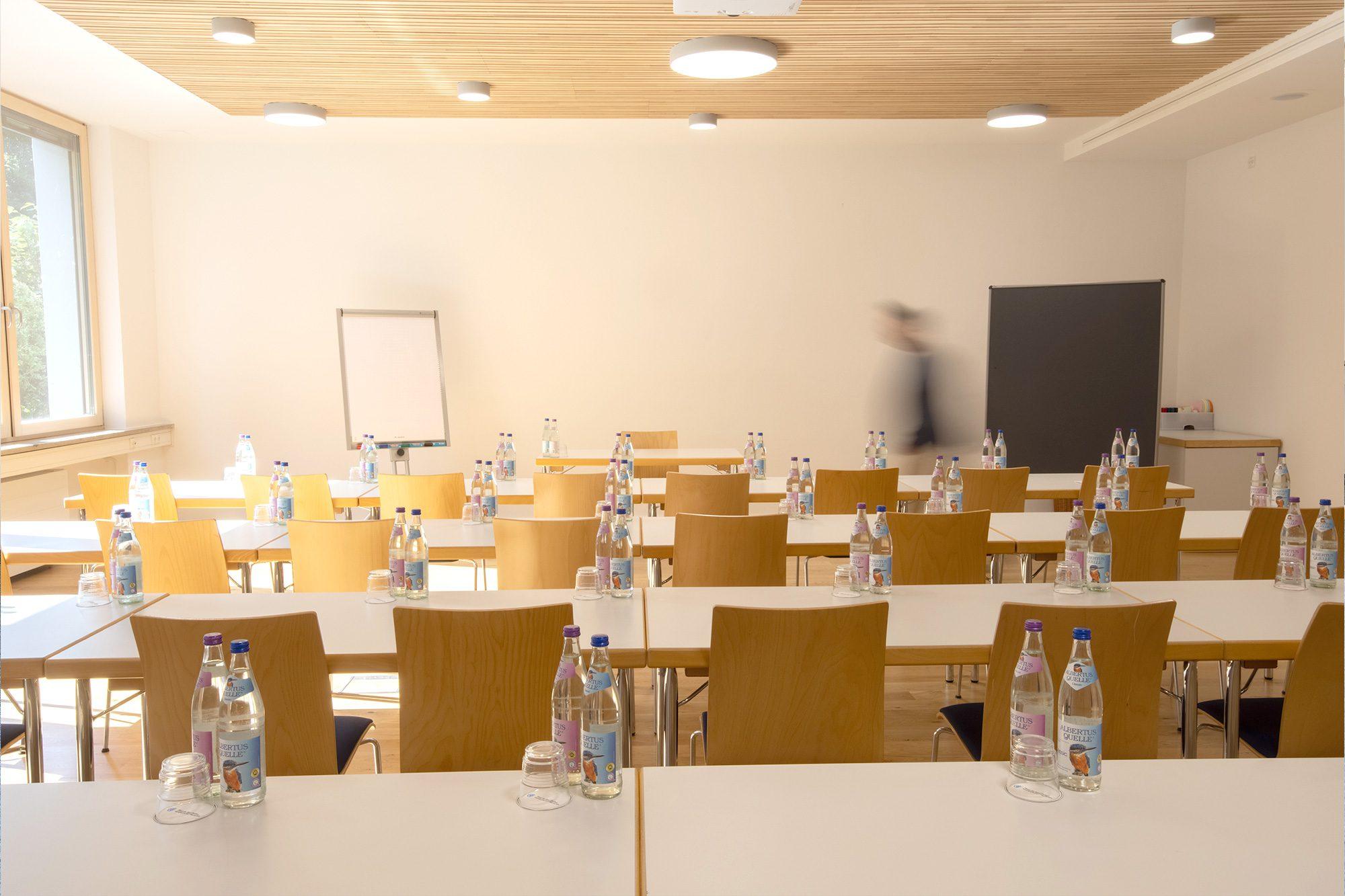 Seminarraum mit Stühlen, Flipchart, einer Pinnwand und Wasserflaschen inkl. Gläsern auf den Tischen
