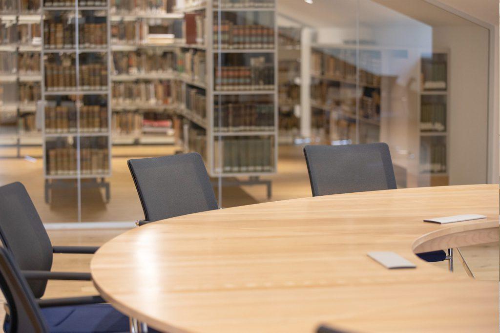 Tisch mit Stühlen und im Hintergrund Bücher in Regalen hinter einer Glaswand
