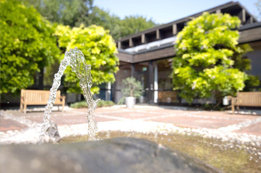 Ein einladender Platz vor dem Tagungszentrum mit Wasser, Holzbänken und Laubbäumen