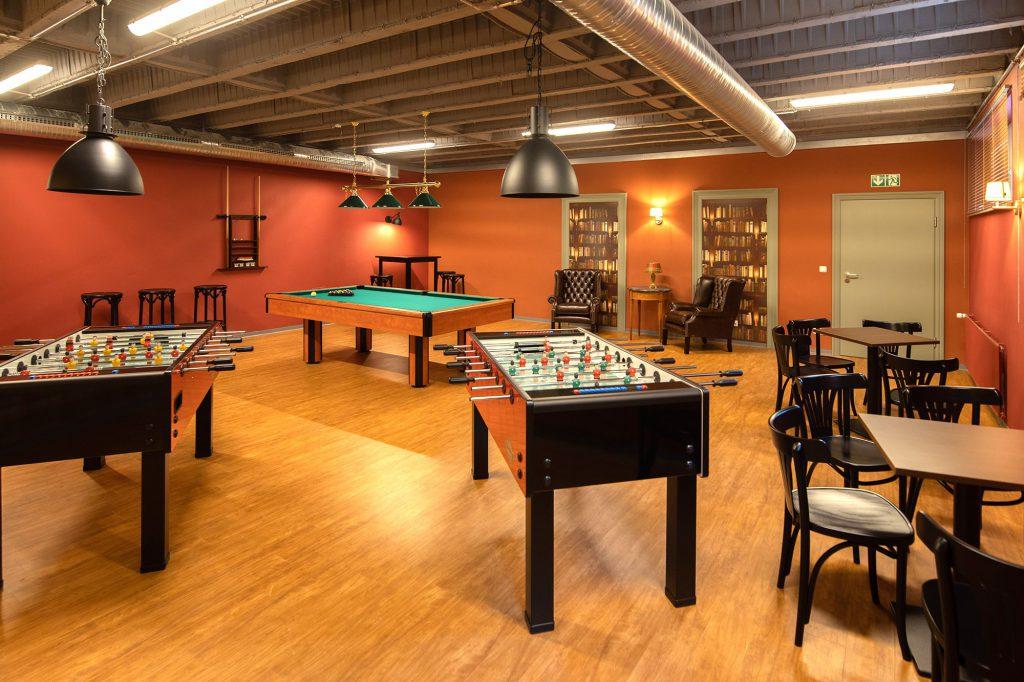 Freizeitraum mit Sitzmöglichkeiten, zwei Tischfußballtischen und einem Billiardtisch