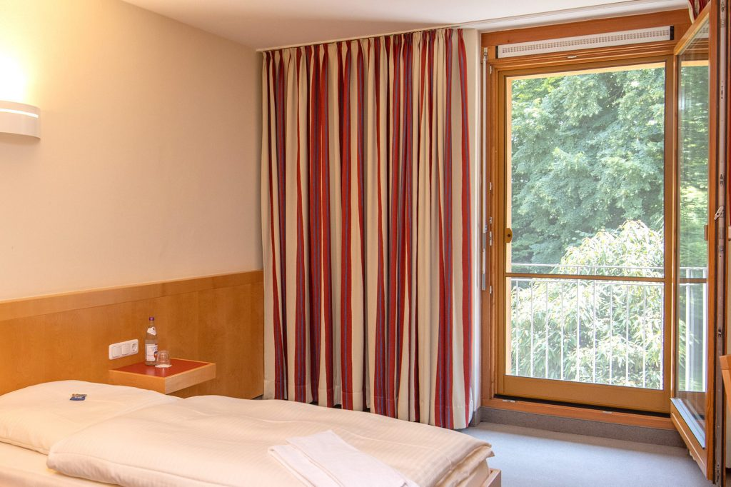 Zimmer mit einem Einzelbett, Nachttisch mit einer Wasserflasche und einer großen Balkontür