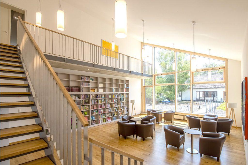 Raum auf zwei Etagen mit Sitzgelegenheiten und einer Bücherwand