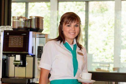 Auszubildende Hauswirtschafterin beim Kaffeeautomaten