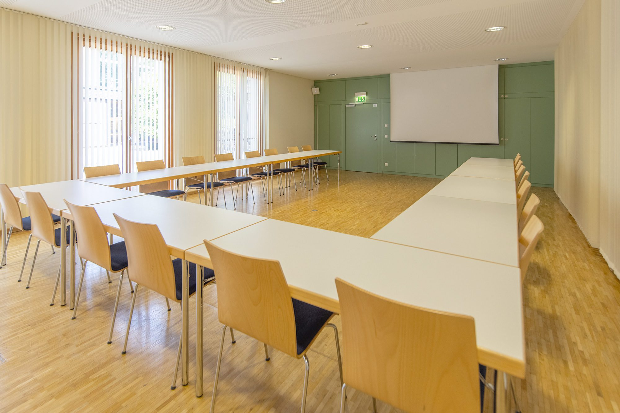 Ein Seminarraum mit Tischen und Sesseln und einer Leinwand