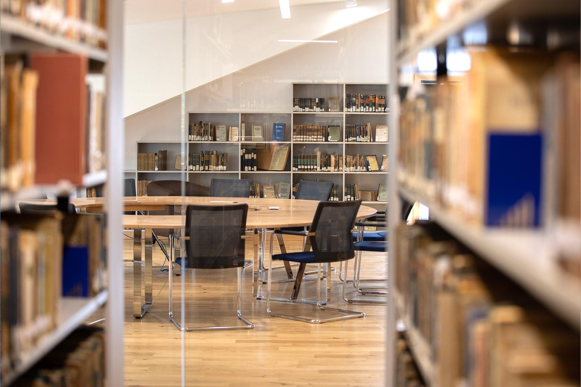 Ein Tisch mit Stühlen umgeben von Regalen gefüllt mit Büchern