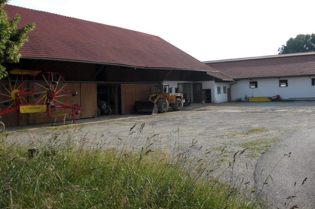 Ein Bauernhof mit diversen Fahrgeräten, einem Schotterparkplatz und einer hohen grünen Wiese.