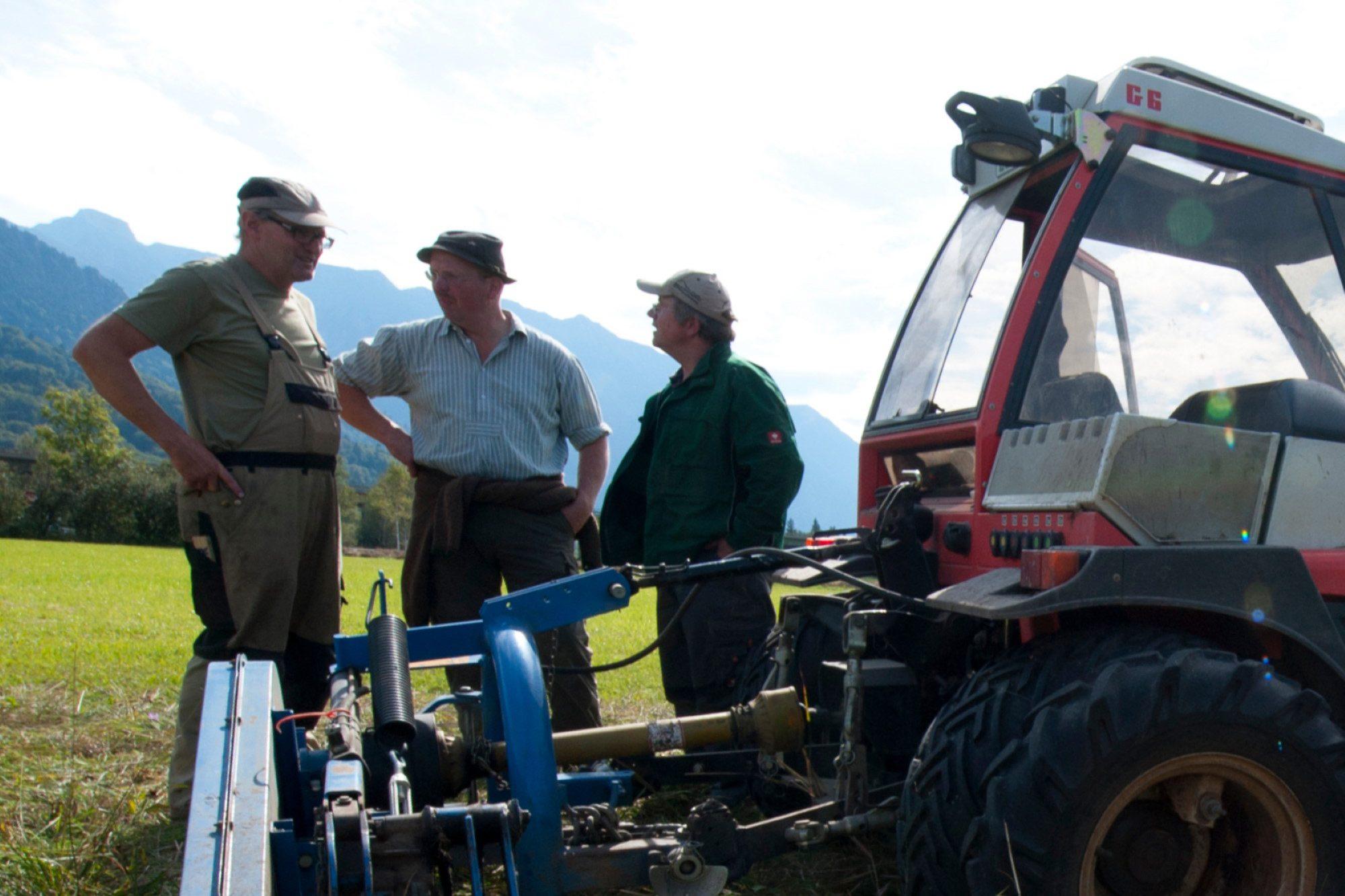 Drei Männer stehen vor einem Traktor und unterhalten sich auf einer Wiese, mit den Bergen im Hintergrund