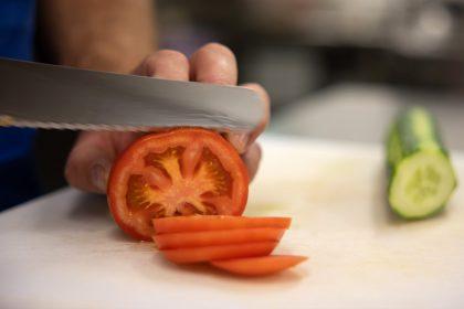 Eine Tomate wird in Scheiben geschnitten und im Hintergrund eine Gurke