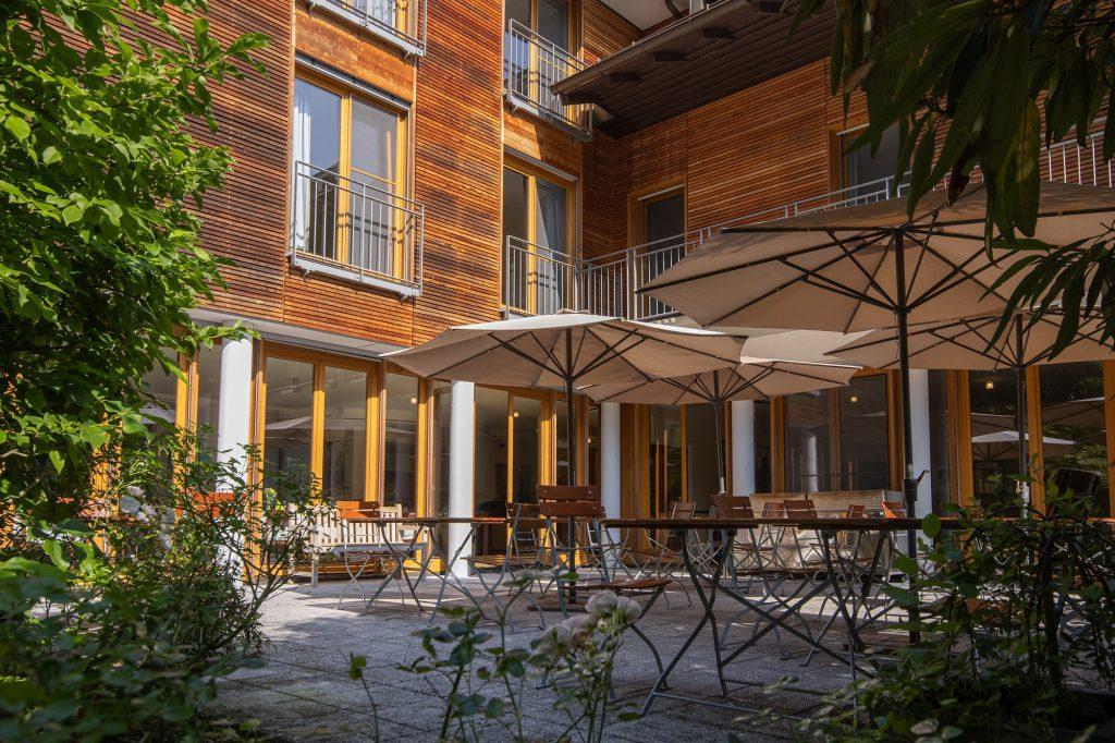 Terrasse mit Tischen, Stühlen und Sonnenschirmen