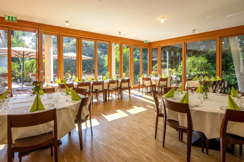 Heller Speisesaal mit gedeckten Tischen und Ausblick in die Natur