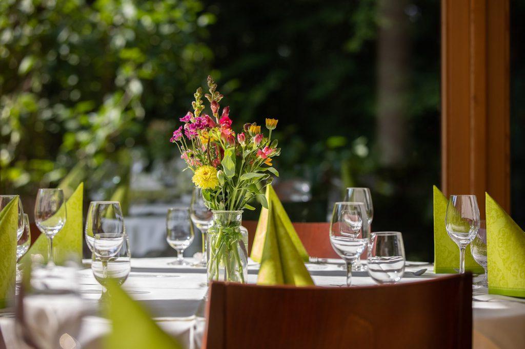 Eingedeckter Tisch mit frischen Blumen in der Mitte