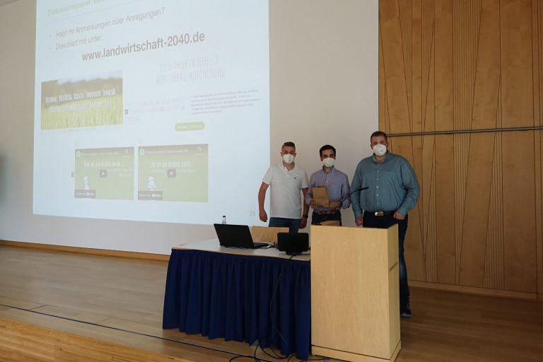 Drei Personen mit FFP2-Maske hinter einem Rednerpult