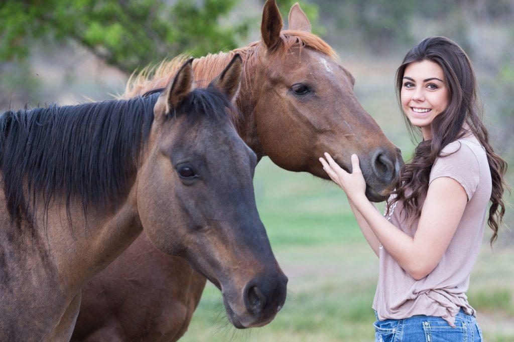 Zwei Pferde und eine lächelnde Frau, die den Kopf eines Pferden anfasst