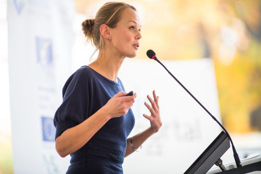 Eine Frau steht vor einem Rednerpult und spricht in ein Mikrofon