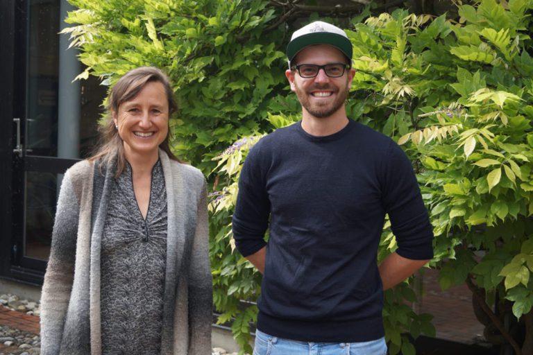 Ein Mann und eine Frau vor grünen Laubbäumen