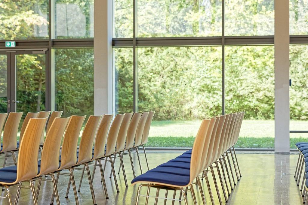 Heller Raum mit großen Glasfronten und Stühlen