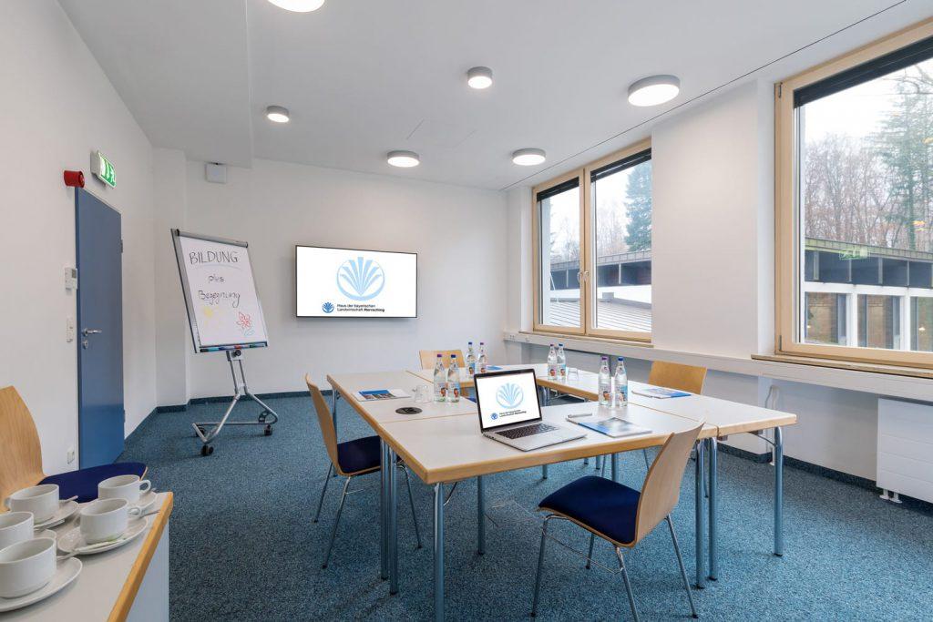 Seminarraum mit einer quadratischen Tischaufstellung, einem Fernsehern und einer Flipchart und zwei Fenstern, die den Raum erhellen