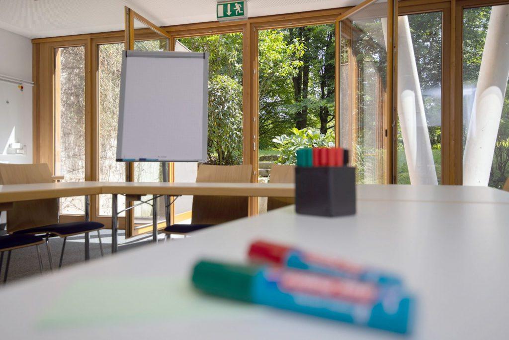 Heller Seminarraum mit offener Balkontür