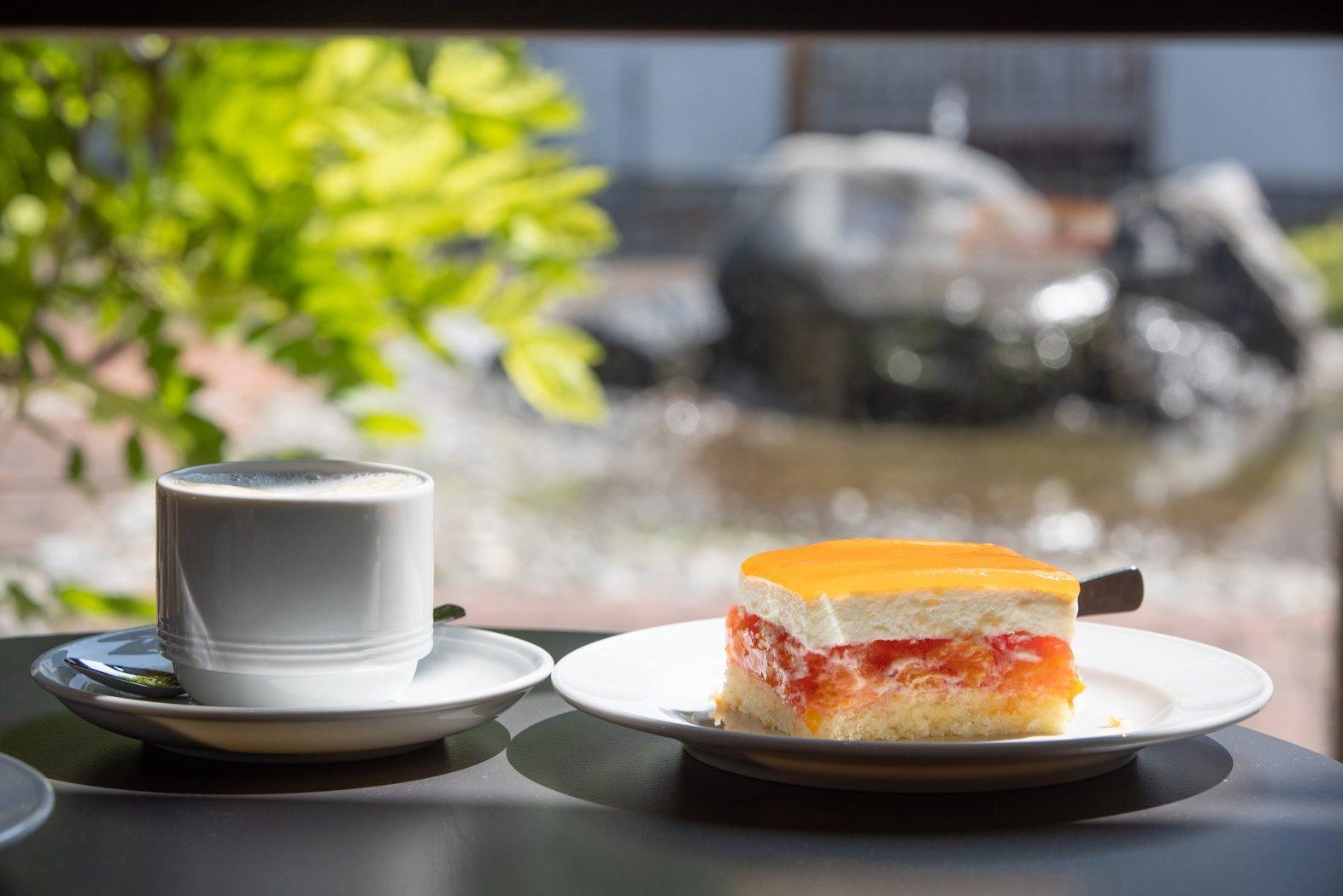 Stück Kuchen und Kaffee mit Hof im Hintergrund