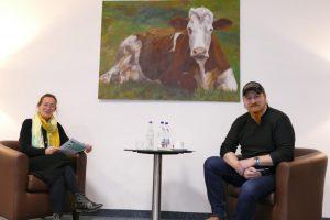 Gespräch zwischen zwei Personen mit einem gemalten Bild von einer Kuh an der Wand